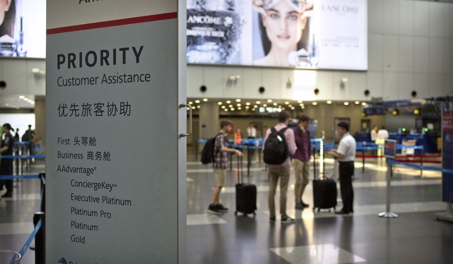 In this July 6, 2018, file photo, travelers stand near a signboard at the American Airlines check-in counters at the Beijing Capital International Airport in Beijing. Chinese regulators appear to have rejected a possible attempt by U.S. airlines at a compromise over Beijing's demand to call self-ruled Taiwan a part of China, an order Washington opposed. (AP Photo/Mark Schiefelbein, File)