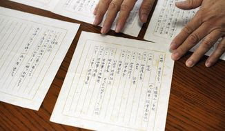 """In this July 26, 2018, photo, Takeo Hatano, a used bookstore owner, shows the five-page """"Yuzawa memo,"""" written by Michio Yuzawa, interior vice minister in 194, in Tokyo. The newly released memo by a wartime Japanese official provides what a historian says is the first look at the thinking of Emperor Hirohito and Prime Minister Hideki Tojo on the eve of the Japanese attack on Pearl Harbor that thrust the U.S. into World War II. (AP Photo/Eugene Hoshiko)"""