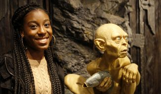 Florida student Tyah-Amoy Roberts poses next to a statue of Gollum Friday, July 27, 2018, at the Weta Workshop movie effects studio in Wellington, New Zealand. The 17-year-old is one of one of 28 students from Marjory Stoneman Douglas High School in Parkland, Fla., who have embraced the South Pacific nation during a trip to learn how to keep a youth movement going long after a tragedy fades from the headlines. (AP Photo/Nick Perry)