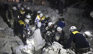 FILE - This Sunday, Jan. 7, 2018 photo provided by the Syrian Civil Defense White Helmets, which has been authenticated based on its contents and other AP reporting, shows Civil Defense workers inspecting a damaged building after a bombing that targeted the office of a militant group consisting of foreign fighters in Idlib, Syria. On Friday, July 27, 2018, The Associated Press has found that stories circulating on the internet that the Pentagon is inviting ISIS terrorists disguised as Syrian White Helmet rescuers to enter the United States are untrue. (Syrian Civil Defense White Helmets via AP)