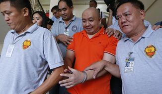 FILE - In this Nov. 7, 2017, file photo, Russell Langi Salic, center, a Filipino doctor accused by U.S. authorities of plotting attacks in New York City, including in concert venues and Times Square, arrives at a trial court for his extradition hearing in Manila, Philippines. A Philippine court on Friday, July 27, 2018, granted a U.S. government request for the extradition of the Filipino doctor suspected by U.S. authorities of being an Islamic State group sympathizer and plotting bombings and shootings at New York City concert venues, subway stations and Times Square. (AP Photo/Bullit Marquez, File)