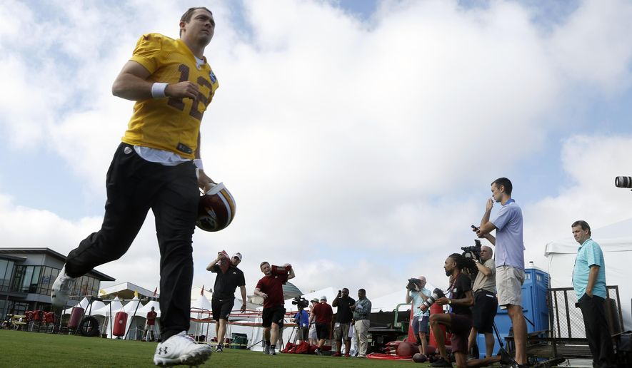 Washington Redskins quarterback Colt McCoy runs to the field at the start of NFL football training camp in Richmond, Va., Thursday, July 26, 2018. (AP Photo/Steve Helber)