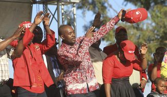 Nelson Chamisa, center, head of the MDC opposition alliance greets supporters at his rally in Chitungwiza about 30 kilometres east of the capital Harare, Thursday, July, 26, 2018. Chamisa addressed his first rally since rejecting the idea of boycotting elections on Monday despite what he calls a biased election commission, in the first election since the November resignation of longtime leader Robert Mugabe. (AP Photo/Tsvangirayi Mukwazhi)