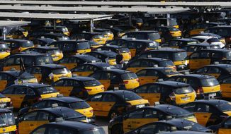 A taxi driver walks between parked taxis during a taxi strike at the Barcelona airport in Prat Llobregat, Spain, Thursday, July 26, 2018. Taxis in Barcelona have begun a 48-hour strike to protest against the growing number of cars operating under ride-hailing apps such as Uber and Cabify. (AP Photo/Manu Fernandez)