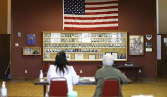 In this June 12, 2018, photo provided by the Wisconsin Center for Investigative Journalism, Julie Routhieaux, administrative specialist for the village of Little Chute, Wis., left, and Patti Seeman, an election inspector, help out with voting at the village hall for a special election in the 1st Senate District. Voting systems in Wisconsin, a key swing state, can be hacked, security experts warn, but local and state officials say not to worry. Wisconsin has seen Russian interference in social media campaigns and attempted hacks of the Democratic Party and government websites. Five election security experts say the state's voting system is vulnerable to interference, citing, among other things, hacking demonstrations that show even offline voting machines can be breached. (Coburn Dukehart/Wisconsin Center for Investigative Journalism via AP)