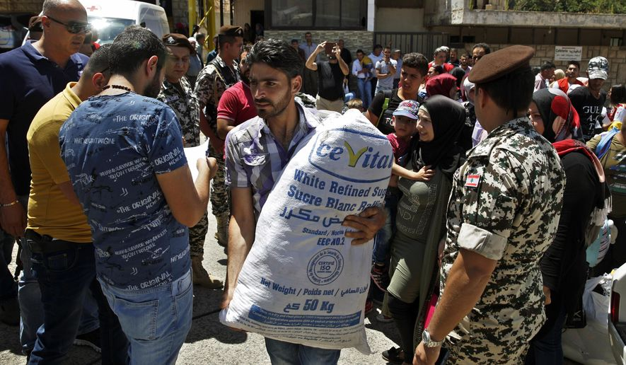 Members of the Lebanese general security organise Syrian refugees gathered to cross into Syria at the Lebanese border crossing point of Masnaa, in Bekaa Valley, Lebanon, Saturday, July 28, 2018. About a thousand Syrian refugees are expected to make the crossing on Saturday, after having requested permission from the Lebanese and Syrian governments. (AP Photo/Bilal Hussein)