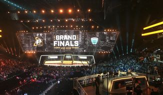 In this Friday, July 27, 2018, fans fill the arena as the stage is set for the Overwatch League Grand Finals' first night of competition, at the Barclays Center in the Brooklyn borough of New York. The Overwatch League is making a grand gamble: that its deep pockets and massive infrastructure can keep it atop the esports mountain even as Fortnite comes charging for the crown. (AP Photo/Terrin Waack)