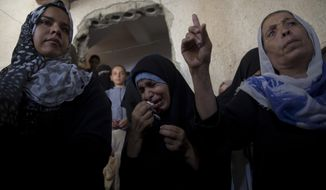 Palestinian relatives of 12 year-old boy, Majdi al-Satari, who was shot and killed by Israeli troops on Friday's ongoing protest at the Gaza Strip's border with Israel, mourn at the family home during his funeral in town of Rafah, Southern Gaza Strip, Saturday, July 28, 2018. Gaza health officials said two Palestinians were killed and dozens injured by Israeli fire at a weekly border protest on Friday. (AP Photo/Khalil Hamra)