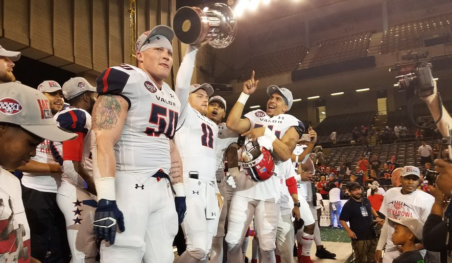Washington Valor backup quarterback Warren Smith (No. 8) holds the Foster Trophy and celebrates with Jimmy Gordon (No. 50) and other teammates after the Valor beat the Baltimore Brigade 69-55 in ArenaBowl XXXI at Royal Farms Arena in Baltimore on Saturday, July 28, 2018. (Photo by Adam Zielonka/The Washington Times)