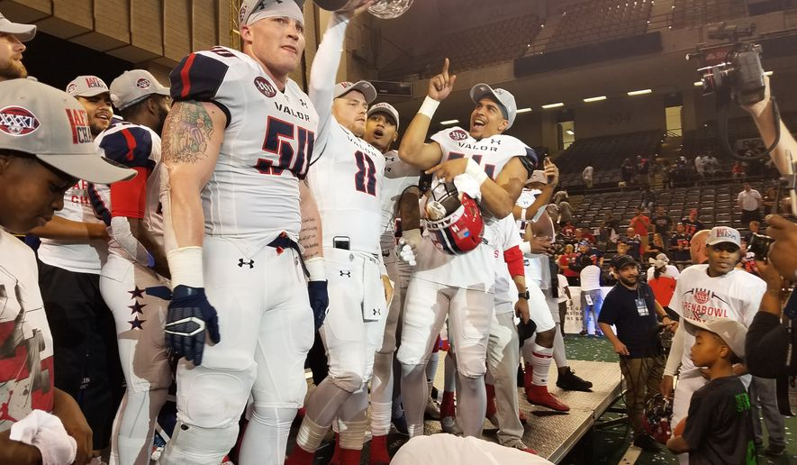Washington Valor backup quarterback Warren Smith (No. 8) holds the Foster Trophy and celebrates with Jimmy Gordon (No. 50) and other teammates after the Valor beat the Baltimore Brigade 69-55 in ArenaBowl XXXI at Royal Farms Arena in Baltimore on Saturday, July 28, 2018. (Photo by Adam Zielonka / The Washington Times)
