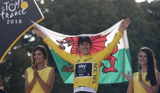 Tour de France winner Britain's Geraint Thomas, wearing the overall leader's yellow jersey and holding of flag of Wales, celebrates on the podium on the Champs-Elysees avenue in Paris,, Sunday July 29, 2018. (AP Photo/Francois Mori)