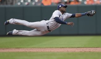Tampa Bay Rays shortstop Adelny Hechavarria stops a ground ball hit by Mark Trumbo in the eighth inning of a baseball game, Sunday, July 29, 2018, in Baltimore. Trumbo earned a single on the play. The Orioles won 11-5. (AP Photo/Gail Burton)