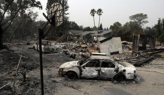 Burned vehicles sit in front of a wildfire-ravaged home, Sunday, July 29, 2018, in Redding, Calif. (AP Photo/Marcio Jose Sanchez)