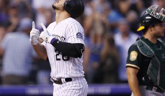 Colorado Rockies' Nolan Arenado, left, gestures as he crosses home plate after hitting a solo home as Oakland Athletics catcher Josh Phegley looks on in the third inning of a baseball game Saturday, July 28, 2018, in Denver. (AP Photo/David Zalubowski)