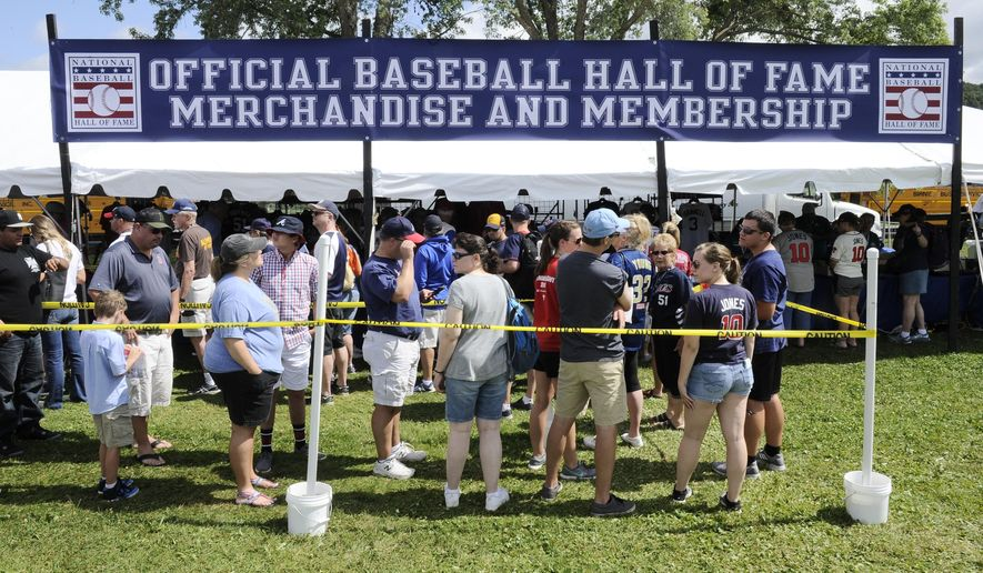 Fans buy baseball merchandise before the start of National Baseball Hall of Fame induction ceremonies Sunday, July 29, 2018, in Cooperstown, N.Y. (AP Photo/Hans Pennink)