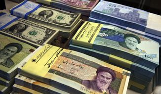 In this April 4, 2015, file photo, Iranian and U.S. banknotes are on display at a currency exchange shop in downtown Tehran, Iran. Iran's currency is continuing its downward spiral as increased American sanctions loom, hitting a new low on the thriving black market exchange. The Iranian rial fell to 112,000 to the dollar on Sunday, July 29, 2018, from 98,000 to $1 on Saturday. (AP Photo/Vahid Salemi, File)