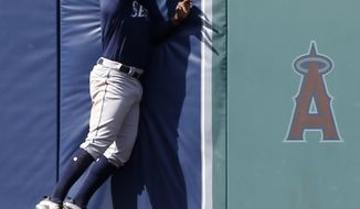 Seattle Mariners left fielder Denard Span leaps at the fence to catch Los Angeles Angels' Andrelton Simmons RBI sacrifice fly ball, to score Justin Upton, during the seventh inning of a baseball game in Anaheim, Calif., Sunday, July 29, 2018. (AP Photo/Alex Gallardo)