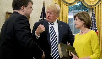 President Donald Trump, pumps his fist as Robert Wilkie, left, accompanied by his wife Julia, right, is sworn in as Secretary of the Department of Veterans Affairs during a ceremony in the Oval Office of the White House, Monday, July 30, 2018, in Washington. (AP Photo/Andrew Harnik)