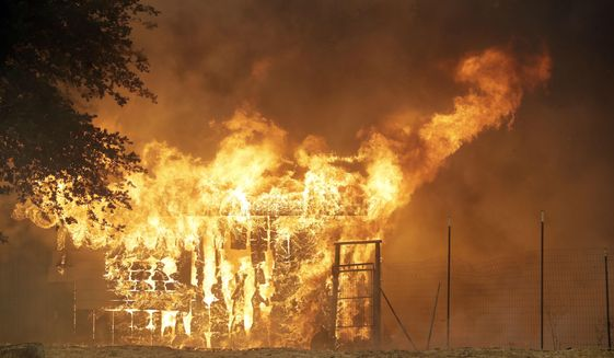 A structure is destroyed by an advancing wildfire, Monday, July 30, 2018, in Finley, Calif. (AP Photo/Marcio Jose Sanchez)