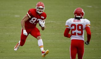 Kansas City Chiefs tight end Travis Kelce (87) tries to evade safety Eric Berry (29) during NFL football training camp Saturday, July 28, 2018, in St. Joseph, Mo. (AP Photo/Charlie Riedel)