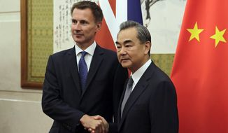Britain's Foreign Minister Jeremy Hunt, left, shakes hands with his Chinese counterpart Wang Yi as they pose for a photograph before their meeting at the Diaoyutai State Guesthouse in Beijing, Monday, July 30, 2018. (AP Photo/Andy Wong, Pool)