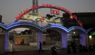 In this March 11, 2018 photo, a man walks past the entrance of Macau (Yat Yuen) Canidrome in Macau. The dog races were held here for half a century, up to five nights a week - a constant in this former Portuguese colony even as high-stakes casinos and concert venues sprouted up to offer newer, glitzier entertainment options. Development and changing tastes have finally caught up with the Yat Yuen Canidrome Club, whose closure July, 2018, means the end of a controversial fixture in Macau - and of legal, regulated dog-racing in Asia. (AP Photo/Kin Cheung)