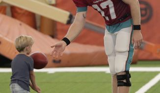 Miami Dolphins quarterback Ryan Tannehill plays with his son, Steel, at the NFL football team's training camp, Monday, July 30, 2018, in Davie, Fla. Tannehill just celebrated his 30th birthday, but he says he feels like he's 25, and that includes his surgically repaired left knee. (AP Photo/Lynne Sladky)