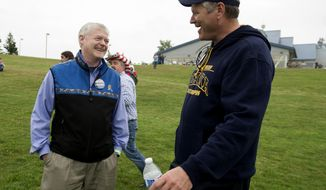 FILE - In this July 26, 2018 file photo, Republican gubernatorial candidates Mead Treadwell, left, and Mike Dunleavy share a laugh during the Alaska Republican Party annual picnic in Anchorage, Alaska. Former Alaska Gov. Sean Parnell says the state needs a course correction and Republican Dunleavy is best suited to lead that effort. Dunleavy and Treadwell are the major candidates competing in the Republican gubernatorial primary on Aug. 21, 2018. (AP Photo/Michael Dinneen, File)