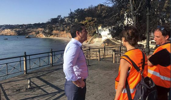 Greece's Prime Minister Alexis Tsipras visits the burnt area of Mati, east of Athens, Monday, July 30, 2018. Fire officials in Greece raised the death toll from a wildfire that raged through the Mati coastal area east of Athens to 91 and reported that 25 people were still missing Sunday. (Greek Prime Minister's Office via AP)