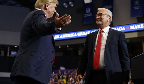 FILE - In this June 27, 2018, file photo President Donald Trump hugs Senate candidate Rep. Kevin Cramer, R-N.D., during a campaign rally in Fargo, N.D. The conservative Koch brothers' network declared July 30, that it will not help elect Cramer, the Republican Senate candidate in North Dakota, turning its back on the GOP in a marquee election — at least for now — after determining that the Republican challenger is no better than the Democratic incumbent Heidi Heitkamp.(AP Photo/Evan Vucci, File)