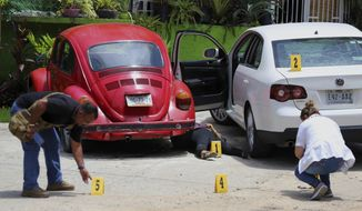 FILE - In this July 22, 2018 file photo, forensics place numbers by evidence near the body of a woman who was found dead between two cars parked outside a restaurant in Acapulco, Mexico. The number of homicides in Mexico in 2017 was higher than originally thought, according to the National statistics institute INEGI, which reports there were 31,174 slayings, not 29,168 reported by the Interior Ministry. INEGI says the homicide rate in 2017 broke down to 25 per 100,000 inhabitants. (AP Photo/Bernandino Hernandez, File)