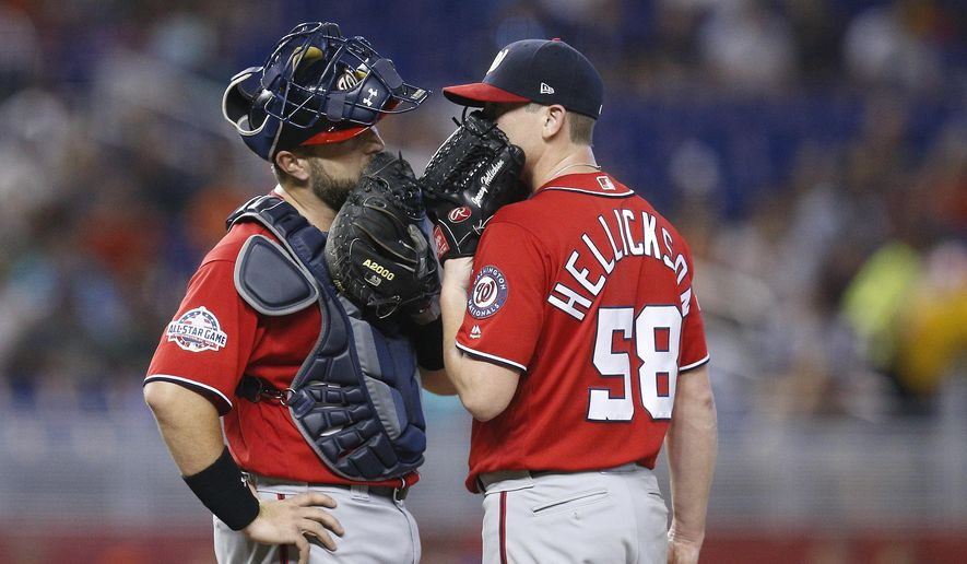 Washington Nationals relief pitcher Jeremy Hellickson, right, and catcher Spencer Kieboom talk on the mound during the third inning of a baseball game against the Miami Marlins, Sunday, July 29, 2018, in Miami. (AP Photo/Brynn Anderson)