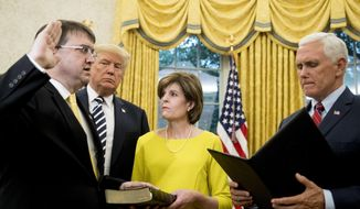 President Donald Trump, second from left, watches as Vice President Mike Pence, right, swears in Robert Wilkie, left, as secretary of the Department of Veterans Affairs during a ceremony in the Oval Office of the White House, Monday, July 30, 2018, in Washington. Also pictured is Wilkie's wife Julia, center. (AP Photo/Andrew Harnik) ** FILE **