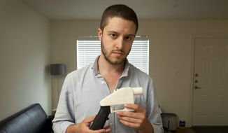 In this May 10, 2013, file photo, Cody Wilson, the founder of Defense Distributed, shows a plastic handgun made on a 3D-printer at his home in Austin, Texas. (Jay Janner/Austin American-Statesman via AP, File)