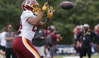 Washington Redskins running back Derrius Guice (29) makes a catch during the morning session of the Redskins NFL football training camp in Richmond, Va., Tuesday, July 31, 2018. (AP Photo/Steve Helber) ** FILE **