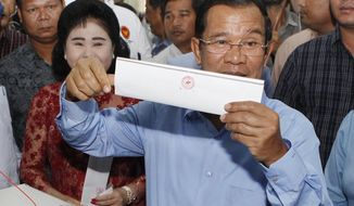 FILE - In this Sunday, July 29, 2018, file photo, Cambodian Prime Minister Hun Sen holds his ballot at a polling station in Takhmua, Kandal province, southeast of Phnom Penh, Cambodia. Determined to extend his 33 years as Cambodia's strongman ruler, Prime Minister Hun Sen was not about to let an election derail what he believes is his destiny. The 65-year-old Hun Sen had declared he intends to stay in office for 10 more years, and Sunday's general election victory by his Cambodian People's Party should get him halfway to that goal. (AP Photo/Heng Sinith, File)