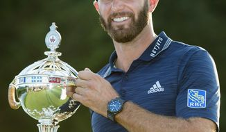 Dustin Johnson, of the United States, hoists the Canadian Open championship trophy at the Glen Abbey Golf Club in Oakville, Ontario, Sunday, July 29, 2018. (Nathan Denette/The Canadian Press via AP)