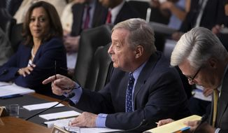 Sen. Dick Durbin, D-Ill., flanked by Sen. Kamala Harris, D-Calif., left, and Sen. Sheldon Whitehouse, D-R.I., questions witnesses as the Senate Judiciary Committee holds a hearing on the Trump administration's policies on immigration enforcement and family reunification efforts, on Capitol Hill in Washington, Tuesday, July 31, 2018. (AP Photo/J. Scott Applewhite)