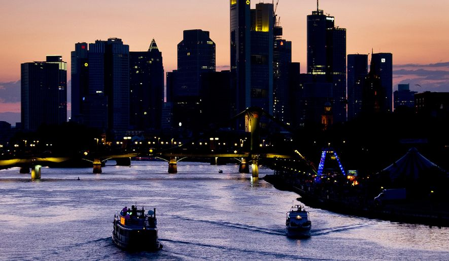 A party ship, left, cruises on the river Main in Frankfurt, Germany, late Saturday, July 28, 2018. (AP Photo/Michael Probst)