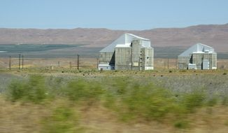 File - This June 13, 2017 file photo shows two decommissioned plutonium-producing reactors on the Hanford Nuclear Reservation near Richland, Wash. The land where the federal government created some of the plutonium for nuclear weapons will be so cleaned of radiation and other pollution that it could be used for homes in the future. The plan announced Monday, July 30, 2018, would spend $200 million to clean up 7.8 square miles in a portion of Hanford called the 100 Area D and H areas. (AP Photo/Nicholas K. Geranios, File)