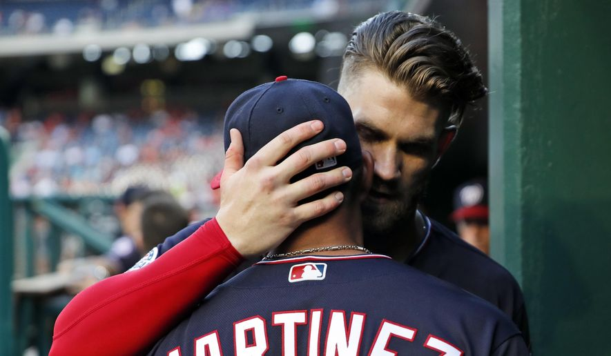 Washington Nationals' Bryce Harper hugs and speaks to manager Dave Martinez before the team's baseball game against the New York Mets at Nationals Park, Tuesday, July 31, 2018, in Washington. (AP Photo/Alex Brandon)