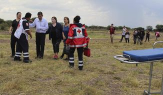 In this photo released by Red Cross Durango communications office, Red Cross workers attend airline passengers who survived a plane crash, as they walk away from the crash site in a field near the airport in Durango, Mexico, Tuesday, July 31, 2018. An Aeromexico jetliner crashed while taking off during a severe storm, smacking down in a field nearly intact then catching fire, and officials said it appeared everyone on board escaped the flames. (Red Cross Durango via AP)