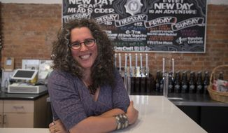 "Tia Agnew, co-founder and CEO of New Day Craft, an Indianapolis-based producer of mead and cider, poses in the tasting room in Indianapolis, Monday, July 30, 2018. Agnew said she was excited to put up her ""Open to All"" window sticker, which she says matches her ""personal and professional ethos."" She's not worried that it will be a turn-off to some potential patrons. (AP Photo/Michael Conroy)"