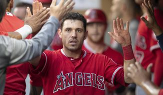 FILE - In this Thursday, July 5, 2018, file photo, Los Angeles Angels' Ian Kinsler is congratulated by teammates in the dugout after scoring against the Seattle Mariners during the fourth inning of a baseball game, in Seattle. In a deal announced late Monday, July 30, 2018, the Boston Red Sox have acquired Kinsler from the Los Angeles Angels to fill in for injured second baseman Dustin Pedroia. (AP Photo/Stephen Brashear, File)