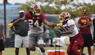 Washington Redskins defensive back Josh Norman (24) covers wide receiver Paul Richardson (10) during the morning session at NFL football training camp in Richmond, Va., Tuesday, July 31, 2018. (AP Photo/Steve Helber) ** FILE **