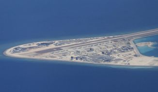 FILE - In this April 21, 2017, file photo, an airstrip, structures and buildings on China's man-made Subi Reef in the Spratly chain of islands in the South China Sea are seen from a Philippine Air Force C-130 transport plane of the Philippine Air Force. Southeast Asian nations are expected to welcome an initial negotiating draft of a nonaggression pact with China on the South China Sea, but critics warn that the protracted talks provide a diplomatic cover for Beijing's tenacious aggression in the disputed waters. Four days of annual summitry in Singapore starts Wednesday, Aug. 1, 2018. (AP Photo/Bullit Marquez, File)