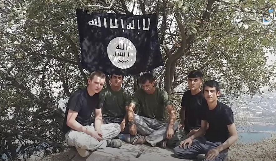 This grab taken from video, made available by Aamaq news agency of the Islamic State group, shows five men sitting on a hill against the backdrop of a black-and-white IS flag and declaring allegiance to IS leader Abu Bakr al-Baghdadi. The Islamic State group on Tuesday July 31, 2018 claimed responsibility for a car-and-knife attack on Western tourists cycling in Tajikistan that killed two Americans and two Europeans. (Aamaq news agency of the Islamic State group via AP)