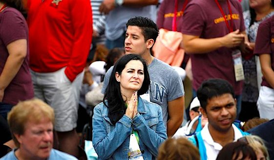 A woman holds her hands in prayer as she watches Pope Francis on a  monitor as people await his arrival on Sept. 26, 2015, in Philadelphia. (Associated Press)