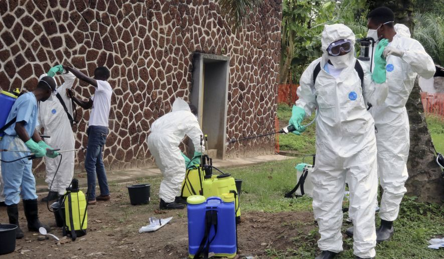 In this Thursday, May 31, 2018, file photo, Congolese health officials prepare to disinfect people and buildings at the general referral hospital in Mbandaka, Congo. (AP Photo/John Bompengo, File)