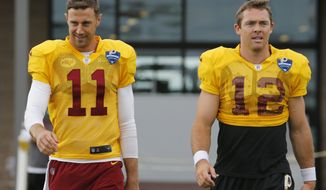 Washington Redskins quarterback Alex Smith (11) and Colt McCoy (12) walk to the field for the morning session of the Redskins NFL football training camp in Richmond, Va., Wednesday, Aug. 1, 2018. (AP Photo/Steve Helber)